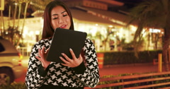 Asian woman using tablet outdoors at night Stock Footage