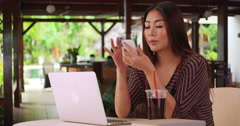 Japanese woman calling a friend for homework help Stock Footage