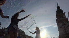 Joyful children playing with many bubbles on public square - blue sky, sunny Stock Footage