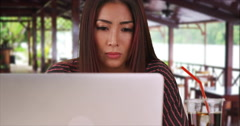 Serious Japanese woman working on laptop in restaurant Stock Footage