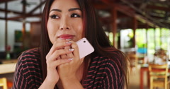 Hopefull Asian woman waiting for her date at a restaurant Stock Footage
