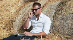 Business man looks beautiful works with a laptop and talking on the phone Stock Footage