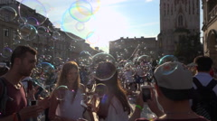 Many soap bubbles blow in wind on crowed square, teens, children - panoramic Stock Footage