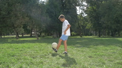 Boy Juggling The Football Or Soccer Ball In The Park On The Lawn, Slow Motion Stock Footage