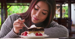 Chinese woman eating cake at a restaurant Stock Footage