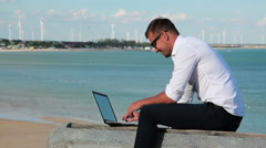 Business man in white shirt and sunglasses with a laptop at the seashore. In the Stock Footage