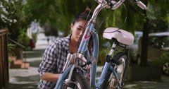 Chinese woman giving her bicycle a quick tuneup Stock Footage