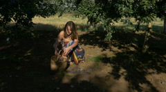 Woman collects ripe plums in the orchard by Pakito. Stock Footage