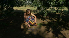 Tilt down from the plums trees to young woman while harvesting fruits by Pakito. Stock Footage