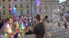 Happy children & teenagers playing with soap bubbles, public square - pan, slow Stock Footage