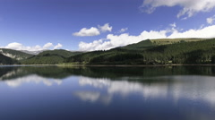 Fly Over Mirror Mountain Lake Surrounded By Forest Stock Footage