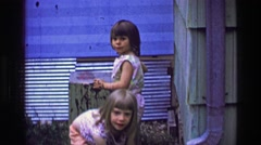 1957: Sisters playing clean mud table surface making art summer vacation. BATON Stock Footage