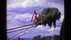 1957: Tractor moving haystack long armed farming machine building high pile. Stock Footage