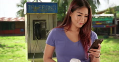 Asian woman using smartphone instead of telephone booth while out travelling Stock Footage