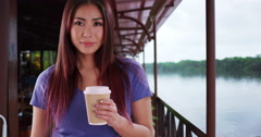 Asian woman standing in a restaurant with coffee Stock Footage