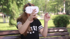 Young woman playing game using VR-helmet for smart phones. Virtual space Stock Footage