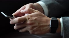Business man using smartphone typing text wearing smart watches on his hand Stock Footage