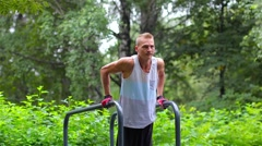 Athletic man is pushed on bars in City Park under summer trees for sport fitness Stock Footage
