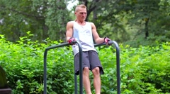 Athletic man exercise the abdominals on bars in City Park under summer trees for Stock Footage
