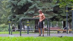 Athletic man doing gymnastics elements on bars in City Park Stock Footage