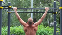 Athletic man doing pull ups on horizontal bar in City Park. rear view. Workout Stock Footage