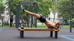 Athletic man exercise the abdominals on bench in City Park under summer trees Stock Footage