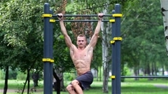 Athletic man doing lifting legs on horizontal bar in City Park. Athletic man Stock Footage