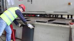Worker cut metal plate on big machine Stock Footage