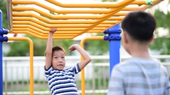 Two young asian boy hang the yellow bar by his hand to exercise at out door play Stock Footage