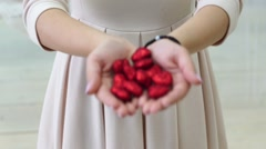 Girl holding decorative hearts in glitter Stock Footage
