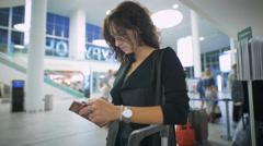 A young lady is thinking about her trip holding her smartphone Stock Footage