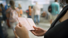A young woman is looking at her visa in the passport Stock Footage