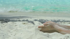 Sand falling from a womans hands in the caribbean Stock Footage