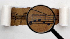 Magnifying glass on music sheet Stock Footage