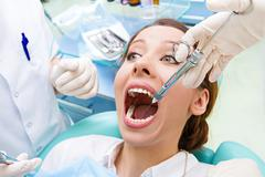 Female patient in dentist office getting anesthesia before tooth  procedure Stock Photos