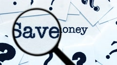 Magnifying glass on save money Stock Footage