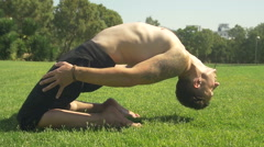 A man on green grass in a sunny park yoga Stock Footage