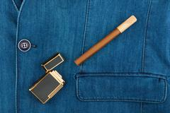 Cigar and lighter lying on a blue denim jacket Stock Photos