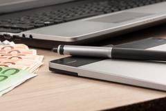 Working businessman desk,stylus, pen tablet, money, as the background Stock Photos