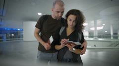 A young couple talking about the trip at the airport Stock Footage