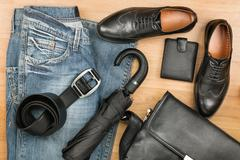 Classic black shoes, briefcase, jeans and umbrella on the wooden floor - stock photo