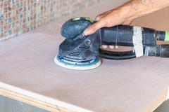 Worker sanding countertop from artificial stone Stock Photos