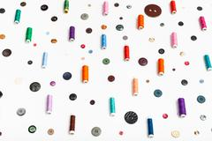 Side view of spools of thread and various buttons Stock Photos