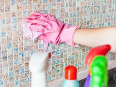 Hand in glove washes ceramic tiles on kitchen wall Stock Photos