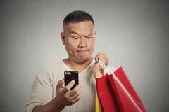 Surprised funny man holding red shopping bags looking at smart phone Stock Photos