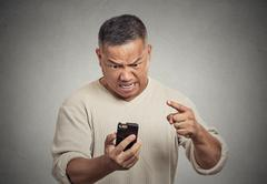 Angry middle aged man while on mobile, pointing at smart phone Stock Photos