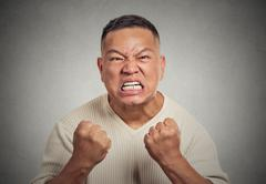 Headshot angry man with open mouth fist up in air aggressive screaming Stock Photos