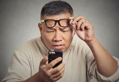 man with glasses having trouble seeing phone screen vision problems - stock photo