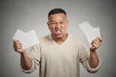 Angry man tearing business documents to pieces Stock Photos