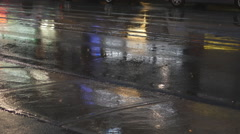 Detail of wet city street on rainy night. Traffic passing by. Stock Footage
